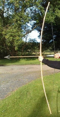 A picture of man shooting with a traditional bow on a outside archery range.