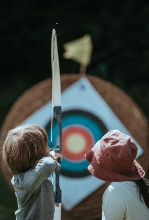 A picture two kids shooting with a bow torwards a target.