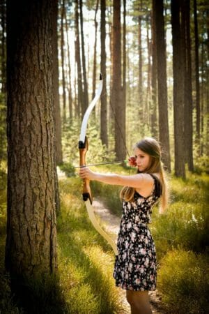 women shooting with a recurve bow outside in the woods in the daylight