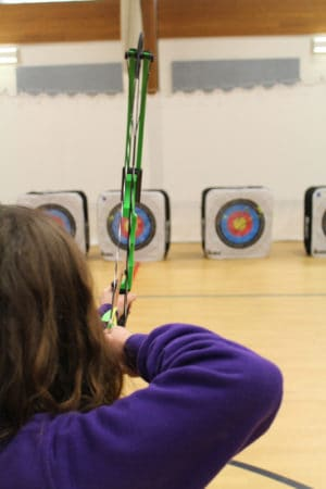 A women shooting with glasses. She is using a compound bow.