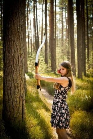 a archery women shooting with a recurve bow with a three stand. She is using the right draw lenght and bow height for her body type.