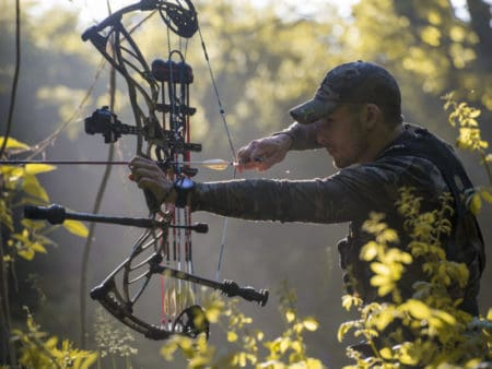 Man shooting with a compound bow with a verticle single pin bow sight in the woods