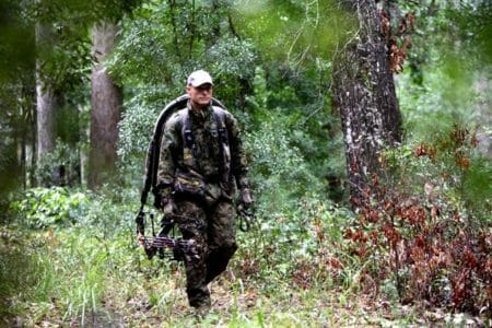 Man walking in the woods with the best crossbow