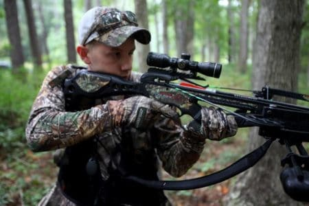 man in the woods with a mini crossbow