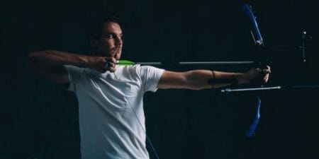 man in white aiming his bow